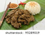 Beef Rendang & Sticky Rice - Malaysian / Indonesian spicy dry beef stew with coconut and sticky rice served on a banana leaf. - stock photo