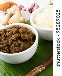 Beef Rendang & Sticky Rice - Malaysian/Indonesian  spicy dry beef stew with coconut served sticky rice. Main dish ingredients on the background (roasted dessicated coconut, ginger and garlic). - stock photo
