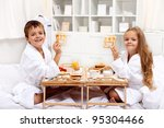 Breakfast in bed with happy kids having a healthy and varied meal - stock photo