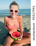 Summer vacation - young girl eating fresh watermelon on sandy beach - stock photo
