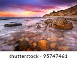 Sunset over rocky beach - stock photo