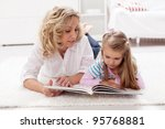 Story telling time - woman and child reading a tale book at home - stock photo