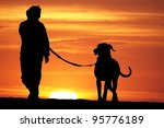 Stock photo silhouette of a young woman walking her great dane dog at sunrise 95776189