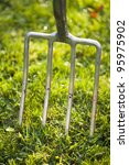 garden fork in a lawn close up - stock photo