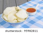 Krupuk Udang - Oriental prawn crackers and sweet chilli sauce dip on a blue gingham tablecloth. - stock photo