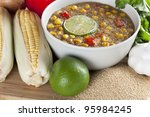 Bowl of amaranth corn chowder surrounded by ingredients. - stock photo