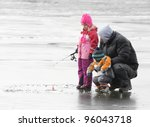 A father teaching his children how to fish on a frozen lake in winter. - stock photo