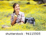 Hiking girl in spring sitting in forest floor flowers. Beautiful woman hiker smiling happy eating an apple during break. Mixed race Asian / Caucasian woman outdoor. - stock photo