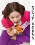 Young girl eating pizza sitting on the floor - stock photo
