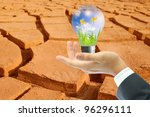 Businessman holding the the light bulb on cracked clay ground into the dry - stock photo