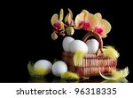Easter sunrise, white eggs and spring yellow orchid with drop of dew - stock photo
