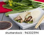 Peking Duck - Chinese peking duck wrapped in pancakes with cucumber, spring onions and hoisin sauce - stock photo