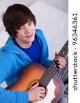 Happy teenager with guitar - closeup - stock photo