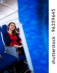 Pretty young female passenger on board of an aircraft (color toned image) - stock photo