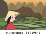 Asian woman smiling while working in rice fields at sunset with mountains behind - stock photo