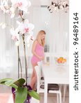 Pregnant woman in kitchen on background. Orchid on foreground. - stock photo