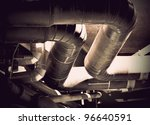 Messy bunch of pipes in industrial building - stock photo