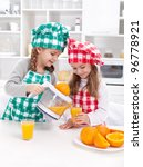 Girls making fresh and healthy orange juice with kitchen appliance - stock photo