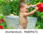 cute baby boy taking water procedures in summer garden - stock photo