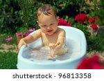 cute funny little boy bathing outdoor in green garden - stock photo