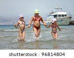 Children running in the sea - stock photo