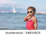Girl with lollipop on the beach - stock photo