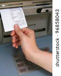 A hand taking a receipt of an Automated Teller Machine, information on the receipt is blurred by photo-editing software. - stock photo