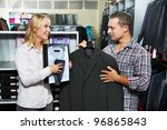 Young couple choosing business suit shirt and necktie during clothing shopping at sales store - stock photo