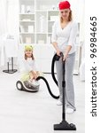 Woman and little girl tidy the room with vacuum cleaner - stock photo