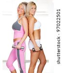 Two beautiful women in fitness outfit using weights - stock photo