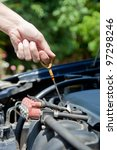 A man inspects the level of oil on a car engine dipstick. - stock photo
