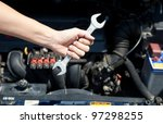 Hand hold wrenches for car repairs service in front of car engine - stock photo