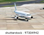 view of commercial airplane parking at an airport - stock photo