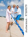 Summer vacation - Tug of war - family playing on the beach - stock photo