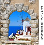 Windmill through an old window in Santorini island, Greece - stock photo