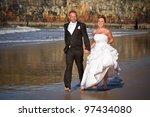 Married couple run on the beach - stock photo