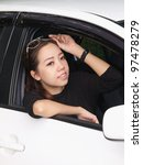 Young pretty Asian girl looking forward of car - stock photo