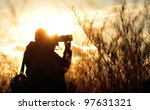 Photographer doing his job in the evening sun. - stock photo