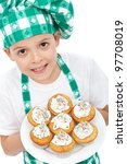 Little boy chef with muffins on a plate - stock photo