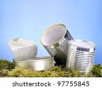 Empty food cans in the grass over blue sky - stock photo