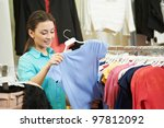 Young woman choosing shirt or blouse during garments clothing shopping at store - stock photo