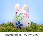 Easter egg in grass with bunny' ears poking out from behind over blue sky - stock photo