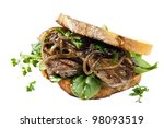 Steak sandwich with onions and spinach, over white background. - stock photo