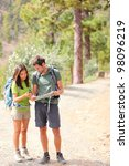 Hikers - hiking couple looking at map using GPS to navigate during camping travel hike. Young Caucasian man and Asian woman. - stock photo