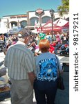 "DAYTONA BEACH, FL - MARCH 17:  Spectators of all ages watch the bikers cruise Main Street during ""Bike Week 2012"" in Daytona Beach, Florida. March 17, 2012 - stock photo"