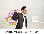 Portrait of a handsome young man with shopping bags - stock photo