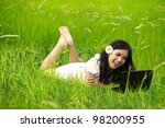 Spring and Summer Collection: Cheerful woman using laptop on green meadow - stock photo