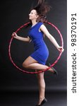 Beautiful woman in a sport wear. Dance hoop gym exercises black background - stock photo