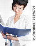 young woman doctor reads papers - stock photo