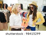 Two Young women with apparel shirt or blouse during garments clothing shopping at store - stock photo